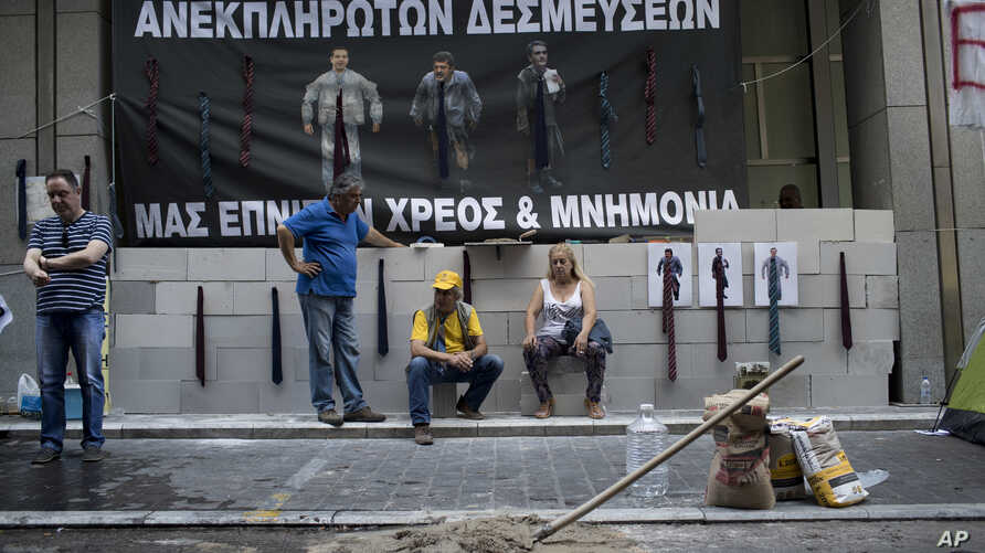 Protesting hospital staff sit in front of a wall that they built at the entrance of the Greek Finance Ministry with a banner depicting Greek Prime Minister Alexis Thipras, Deputy Health Minister Pavlos Polakis and Greek Finance Minister Euclid Tsakal