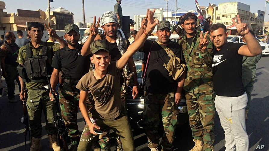 Iraqi security forces and volunteers celebrate in front of Governorate Council Building in Kirkuk, Oct. 16, 2017.