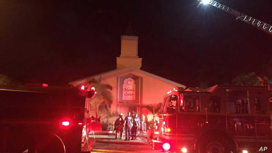 In this photo provided by the St. Lucie Sheriff's Office, firefighters work at the scene of a fire at the Islamic Center of Fort Pierce in Fort Pierce, Florida, Sept. 12, 2016.