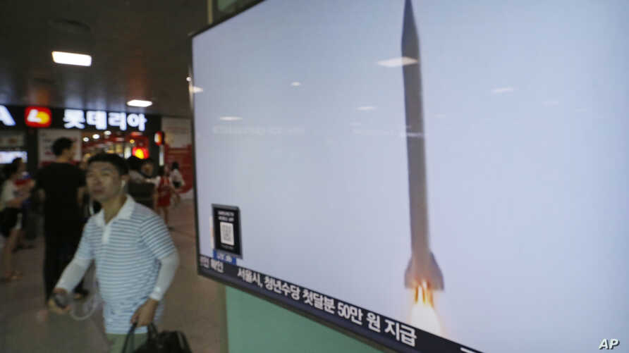 A man passes by a TV news program with  file footage of a North Korean rocket launch at the Seoul Railway Station in Seoul, South Korea, Wednesday, Aug. 3, 2016.