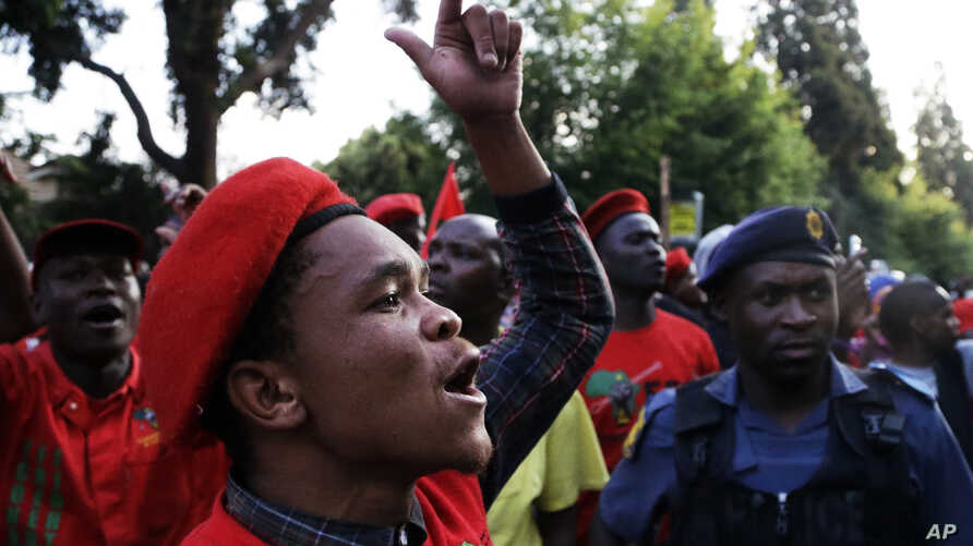 Members of the Economic Freedom Fighters (EFF) party sing during their march for economic reform outside the Johannesburg Stock Exchange, Oct 27, 2015.