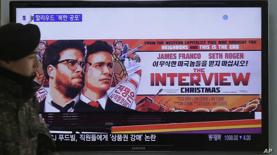 """A South Korean army soldier walks near a TV screen showing an advertisement of Sony Picture's """"The Interview,"""" at the Seoul Railway Station in Seoul, South Korea, Monday, Dec. 22, 2014. North Korea hates the Hollywood film that revolves around the as"""