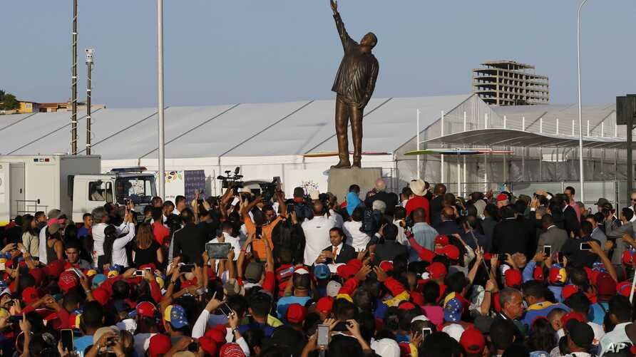 Government supporters attend the ceremony unveiling the statue of Venezuela's late President Hugo Chavez during the 17th Non-Aligned Summit, a meeting held by a Cold War-era group of 120 nations, in Porlamar on Margarita Island, Venezuela, Sept 16, 2