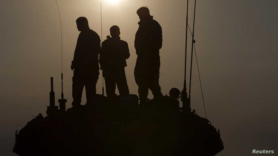 Israeli soldiers stand atop a tank near the border with Gaza, July 29, 2014.