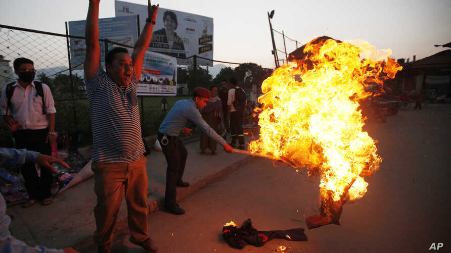 A Nepalese policeman tries to put off the burning effigy of Indian Prime Minister Narendra Modi during a protest by Nepalese youth in Kathmandu, Nepal, Sept. 30, 2015.