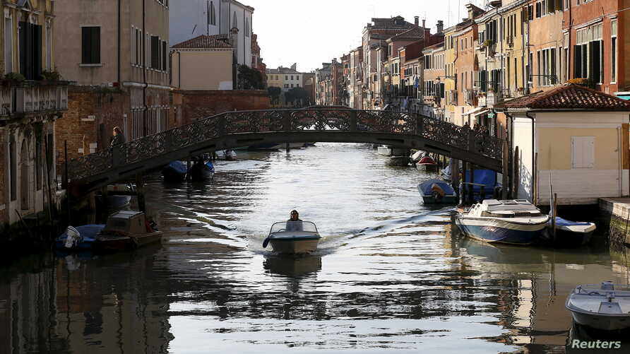 A bridge that once separated the Venice ghetto (L) from Catholic Venice (R) is seen as a boat passes northern Italy, March 22, 2016.