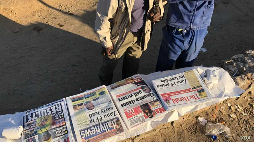 Zimbabwean men reading newspaper headlines, Wednesday morning two days after the country held its first general election without founding leader Robert Mugabe on the ballot.