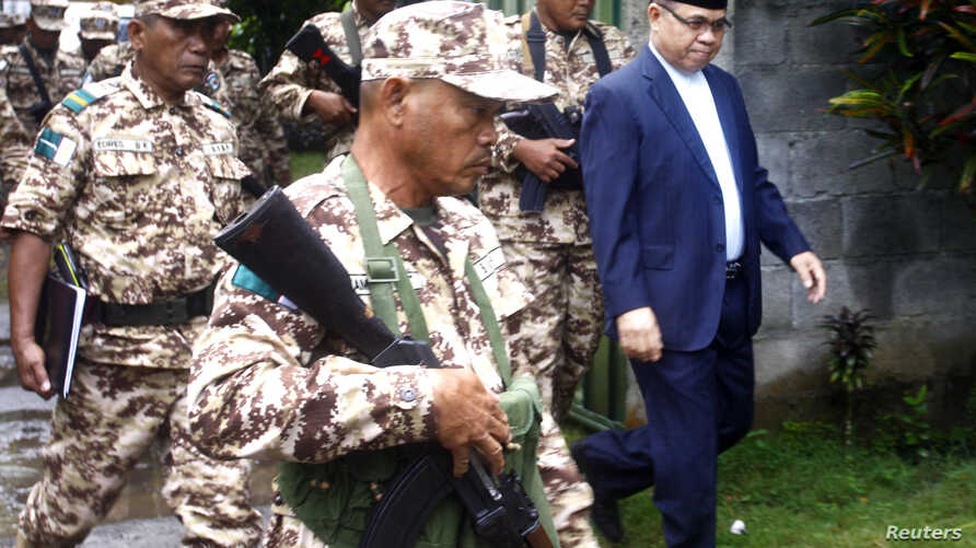 Murad Ebrahim, chairman of the Moro National Liberation Front, walks with his security group before the start of anews conference inside their camp at Sultan Kudarat in Maguindanao province, southern Philippines, September 5, 2011.