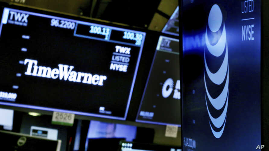 FILE - In this June 13, 2018, file photo, the logos for Time Warner and AT&T appear above alternate trading posts on the floor of the New York Stock Exchange.