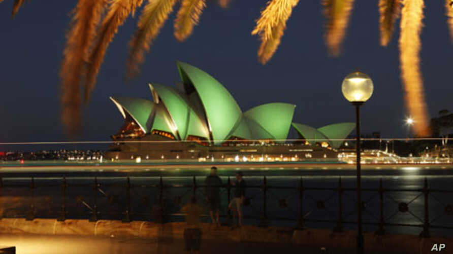 Tourists take pictures in this long exposure photograph as the Sydney Opera House is lit with green lights during St Patrick's Day celebrations in central Sydney, March 17, 2010.