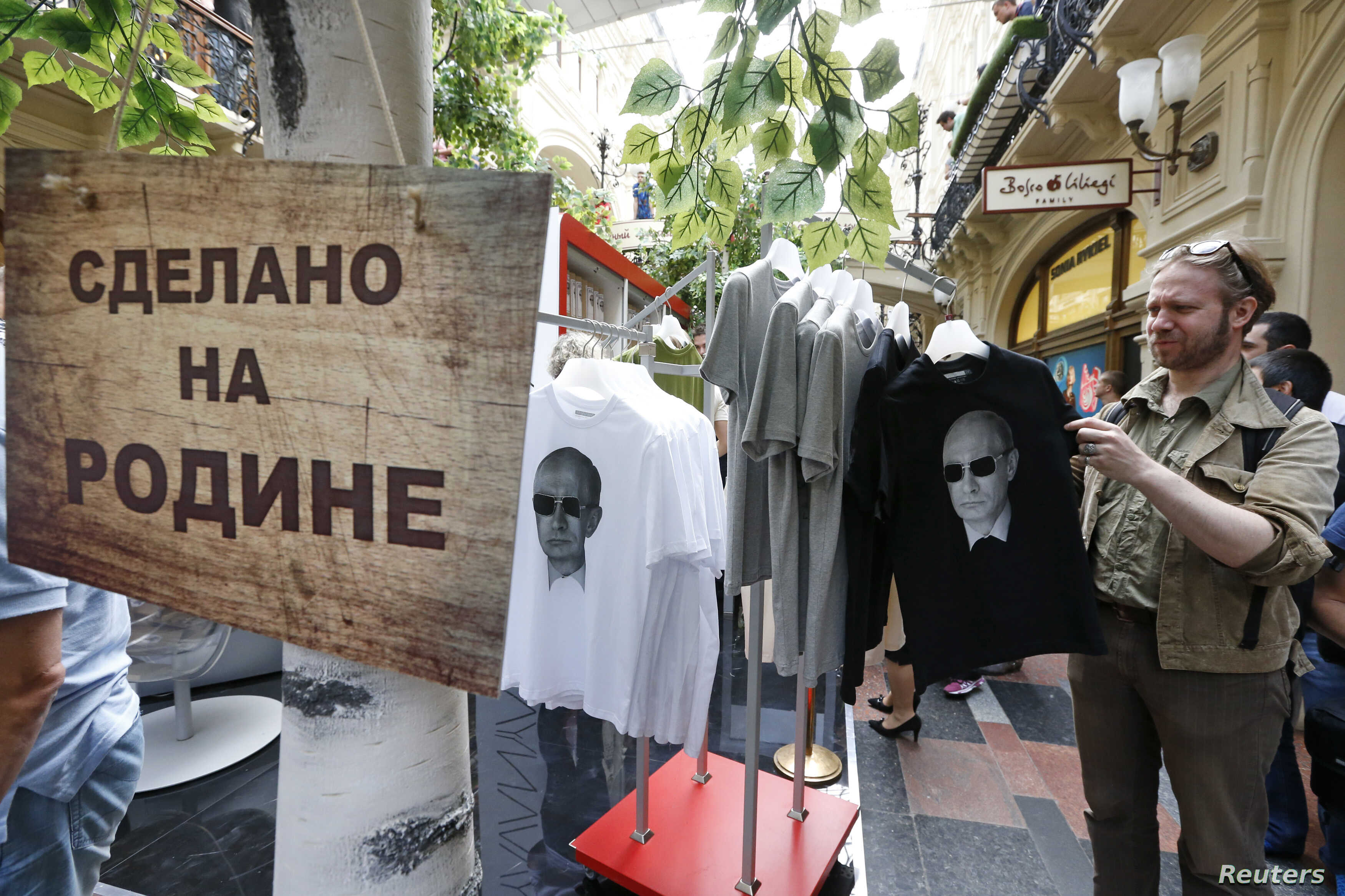 """FILE - T-shirts, displaying images of Russia's President Vladimir Putin, are on sale at GUM department store in central Moscow, June 11, 2014. The sign reads """"Made in Fatherland""""."""