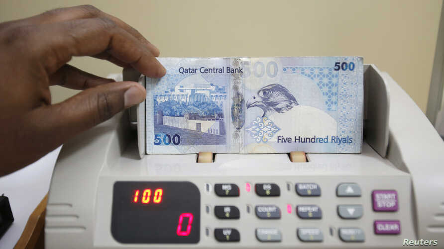 FILE - A cashier counts Qatari riyal notes at a money changer in Doha, May 28, 2013.