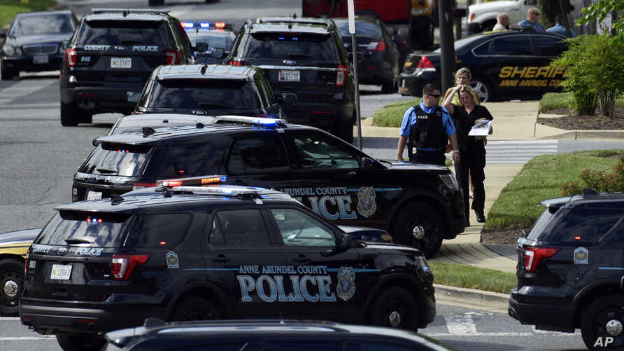 Police secure the scene of a shooting at the building housing the Capital Gazette newspaper in Annapolis, Md., June 28, 2018.