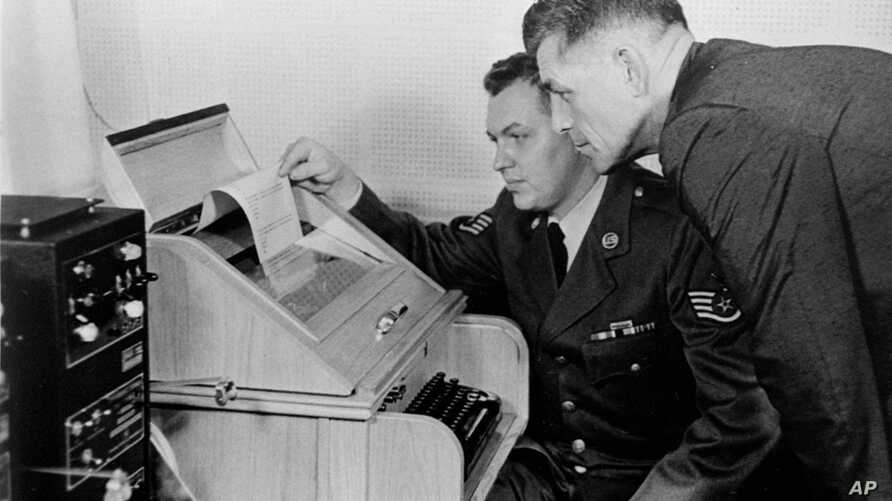 "This Aug.30, 1963 black-and-white file photo shows the White House Kremlin ""hot line"" providing direct communication for emergency use by the Chief of Staff in Washington and Moscow, becaming operational. Air Force Sgt. John Bretoski, left, and Army"