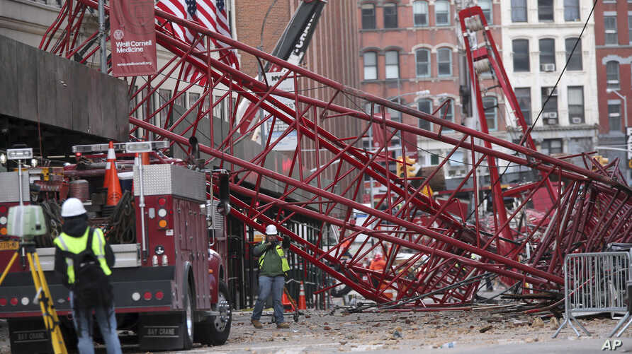 Firefighters and construction crews work on clearing a collapsed crane in New York, Feb. 6, 2016.