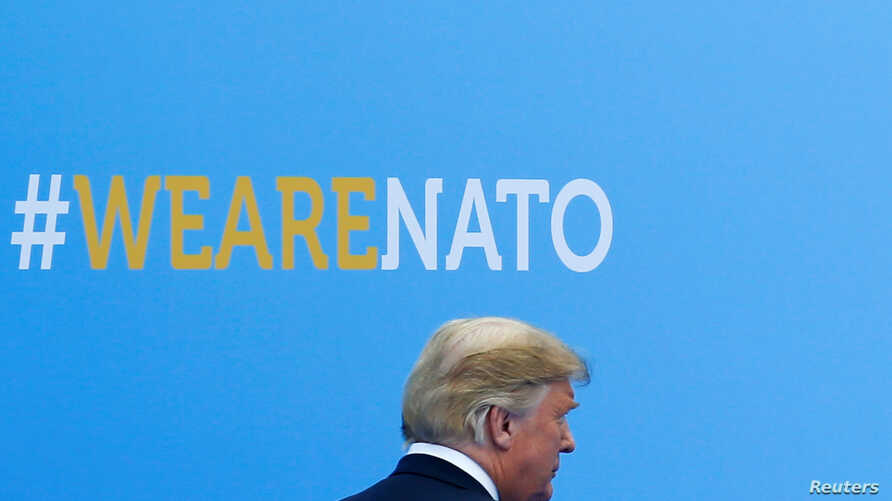 U.S. President Donald Trump walks during the welcoming ceremony at the start of a NATO summit at the Alliance's headquarters in Brussels, Belgium, July 11, 2018.