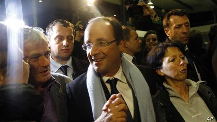 Socialist candidate Francois Hollande, center, arrives at Brive airport in Brive, Central France, after the first round of the presidential election, April 22, 2012.
