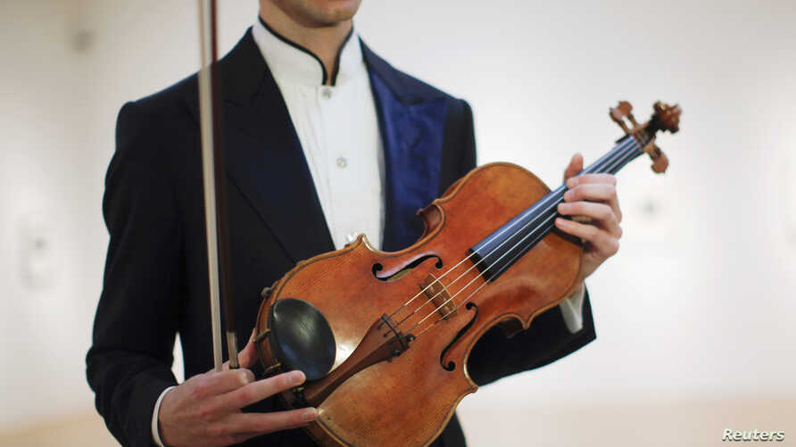 Violist David Aaron Carpenter of the U.S. holds the 'Macdonald' Viola by Antonio Stradivari, made in 1719, at Sotheby's gallery in New York, March 27, 2014.