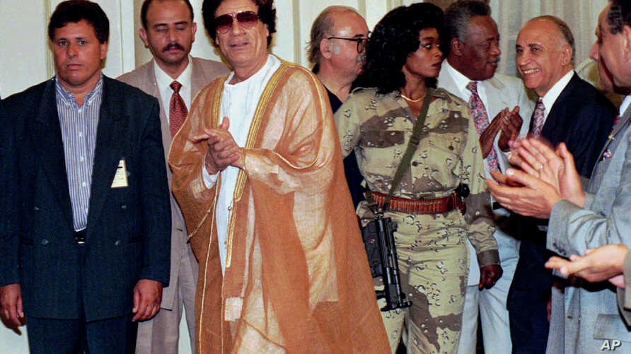 Libyan leader Muammar Gadhafi (C) arrives at Cairo university for a meeting with university professors, The armed woman to the right of Gaddafi is his personal bodyguard, May 27, 1996.