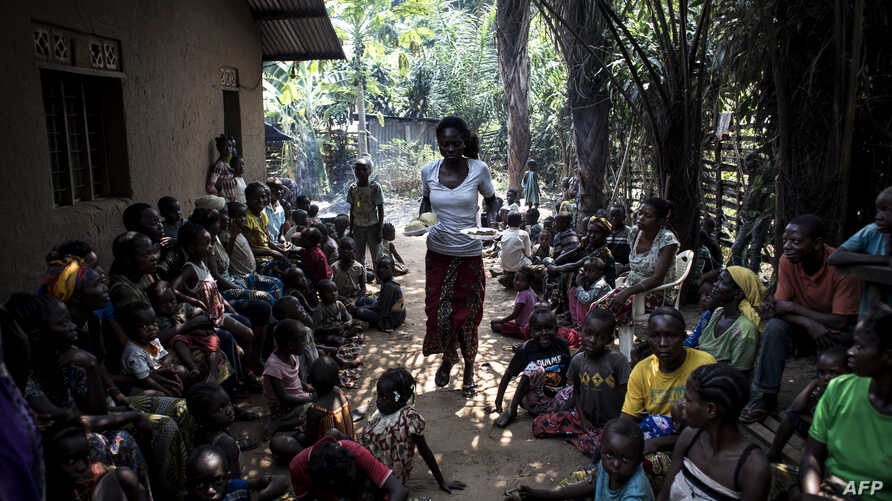 A volunteer brings daily food rations for internally displaced persons (IDPs), at a camp for IDPs fleeing the conflict in the DRC's Kasai province, June 7, 2017, in Kikwit, DRC.