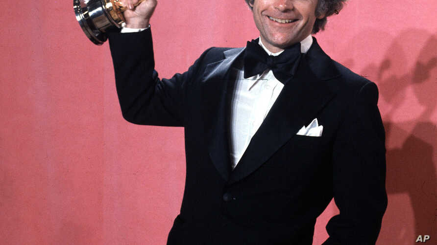 """FILE - John C. Avildsen shows off the Oscar he won for best director for """"Rocky,"""" at the Academy Awards in Los Angeles, March 28, 1977. Avildsen has died at age 81."""