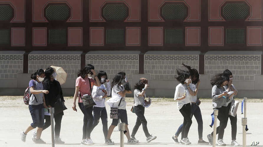 South Korean middle school students wear masks as a precaution against Middle East Respiratory Syndrome (MERS) virus as they visit Gyeongbok Palace in Seoul, South Korea, Wednesday, June 3, 2015.