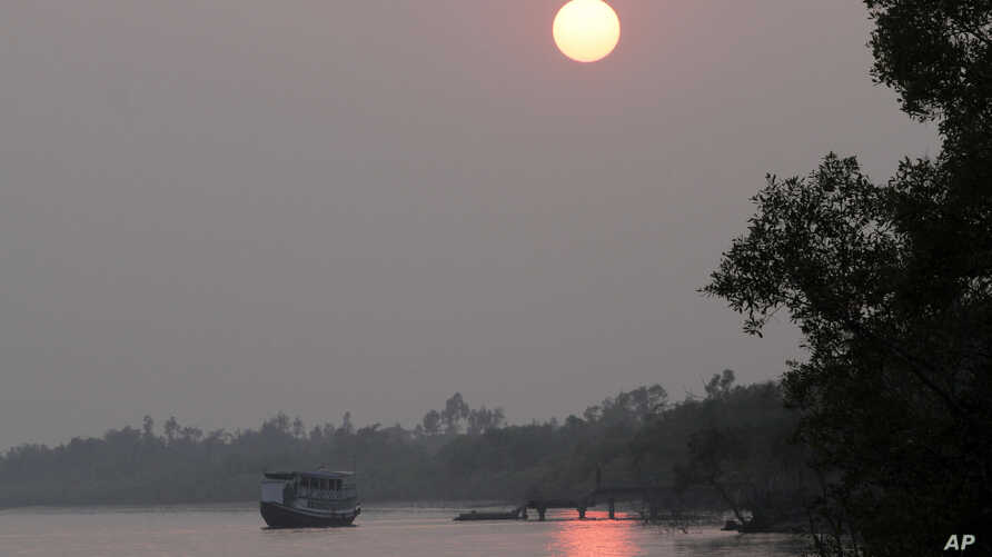 A ferry carrying tourists moves towards a jetty at Bali village in the Sundarbans, India, Jan. 31, 2015. Thousands are homeless as seas rise twice as fast as the global average and water eats away at the islands in this vast region called the Sundarb