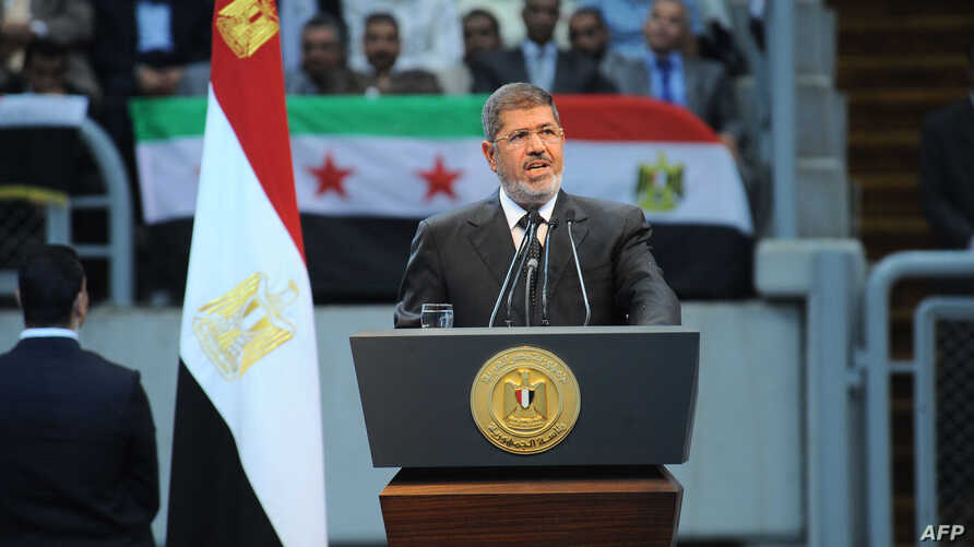 "In this handout picture Egyptian President Mohammed Morsi gives a speech to thousands of Islamists and Syrian opposition supporters during  the ""support for Syria"" rally at Cairo stadium, June 15, 2013 in Cairo, Egypt. (Credit: Ho/Egyptian Presidency"