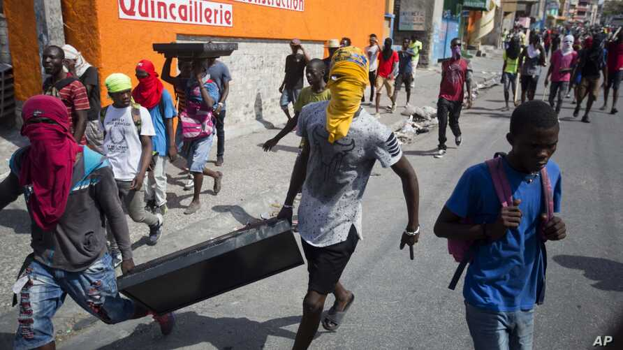 Masked looters carry a flat screen TV amid protests demanding the resignation of Haitian President Jovenel Moise near the presidential palace in Port-au-Prince, Haiti, Feb. 13, 2019.