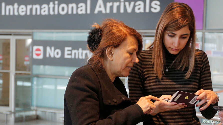 FILE - Negar Jourabchian looks at her mother Niloufar's passport after she traveled to the U.S. from Iran following a federal court's temporary stay of President Trump's travel ban, at Logan Airport in Boston, February 6, 2017.