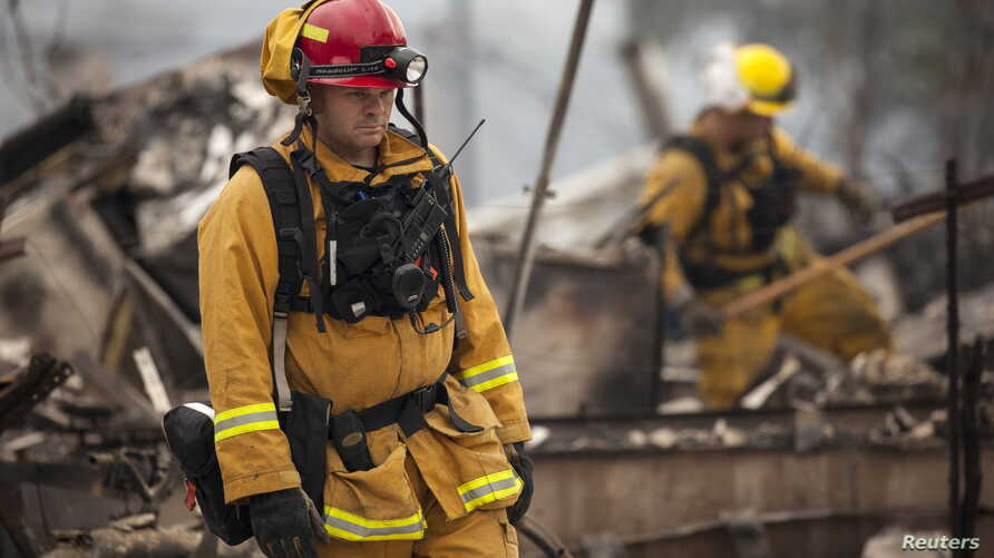 Firefighters search for victims in the rubble of a home burnt by the Valley Fire in Middletown, California, Sept. 14, 2015.