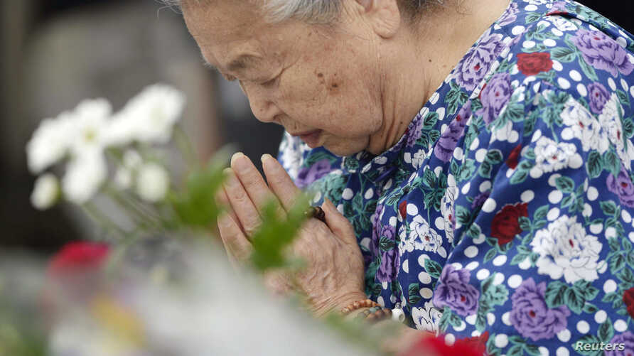 A woman prays for the victims of the 1945 atomic bombing, in the Peace Memorial Park in Hiroshima, in this photo taken by Kyodo, August 6, 2014.
