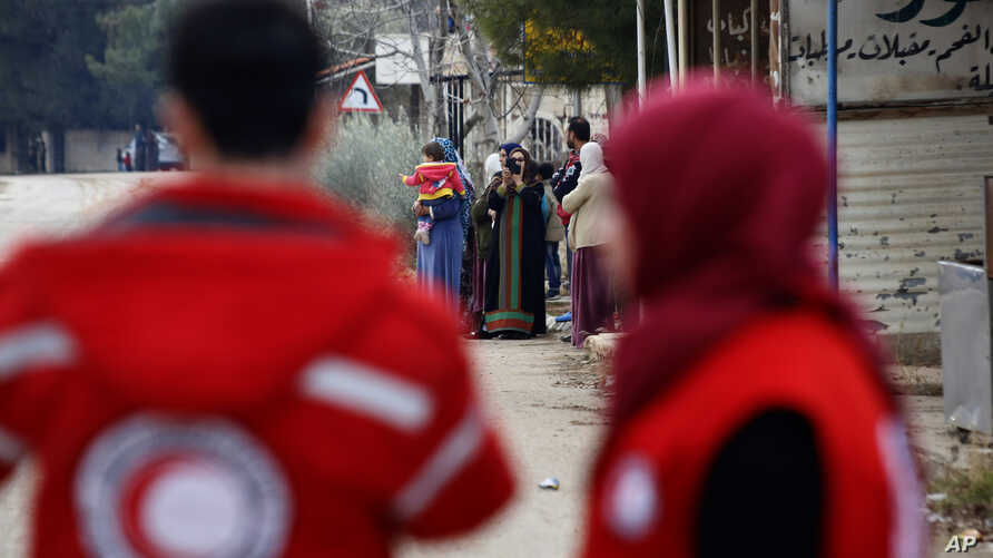 FILE - Members of the Syrian Red Cross stand near aid vehicles loaded with food and other supplies that  entered the besieged town of Madaya about 15 miles (24 kilometers) northwest of Damascus, Syria, Jan. 11, 2016.