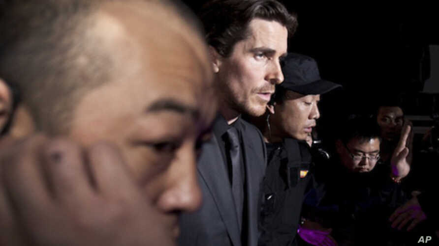 """In this photo taken on Monday, Dec. 12, 2011, actor Christian Bale, center, is led by security guards upon arrival for an event of the Zhang Yimou-directed movie """"The Flowers of War"""" in Beijing, China."""