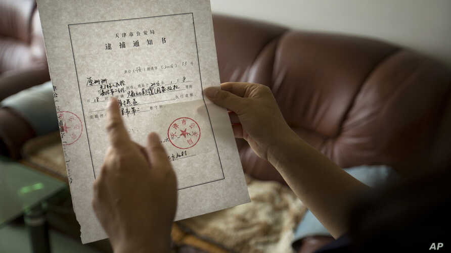 China Lawyers Crackdown: In this Wednesday, July 6, 2016 photo, Yuan Shanshan, the wife of detained Chinese lawyer Xie Yanyi, holds an official notice of Xie's detention from the Tianjin Public Security Bureau in their apartment in Miyun, on the outs