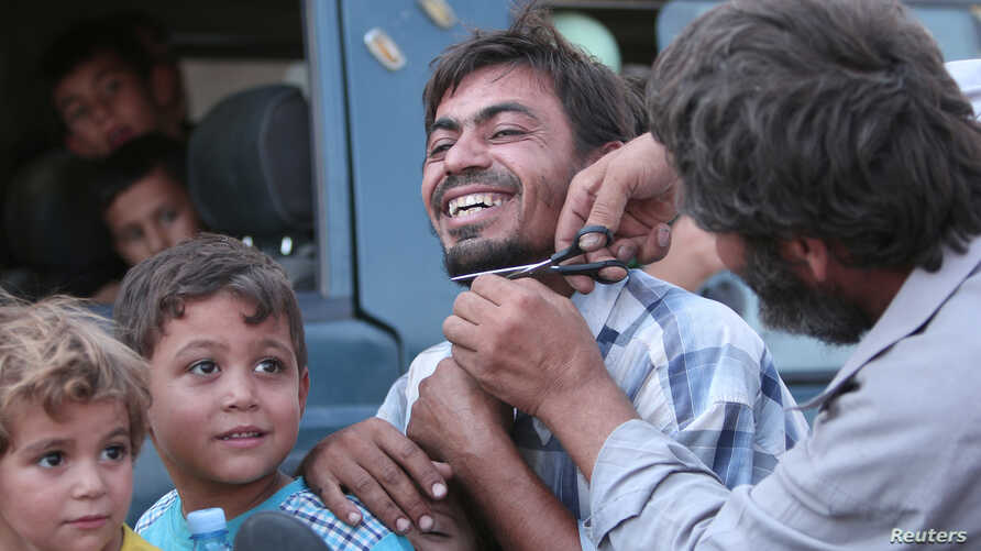 A man cuts the beard of a civilian who was evacuated with others by the Syria Democratic Forces (SDF) fighters from an Islamic State-controlled neighborhood of Manbij, in Aleppo Governorate, Syria, Aug. 12, 2016.