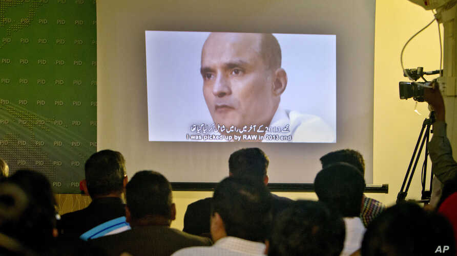 Journalists look a image of Indian naval officer Kulbhushan Jadhav, who was arrested in March 2016, during a press conference by Pakistan's army spokesman and the Information Minister, in Islamabad, Pakistan, March 29, 2016.