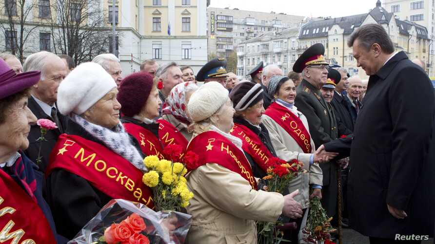 Ukrainian President Viktor Yanukovich (R) greets veterans during a ceremony to mark the day of Ukraine's liberation from Nazi invaders during World War Two on the day of the parliamentary elections in Kiev, October 28, 2012.