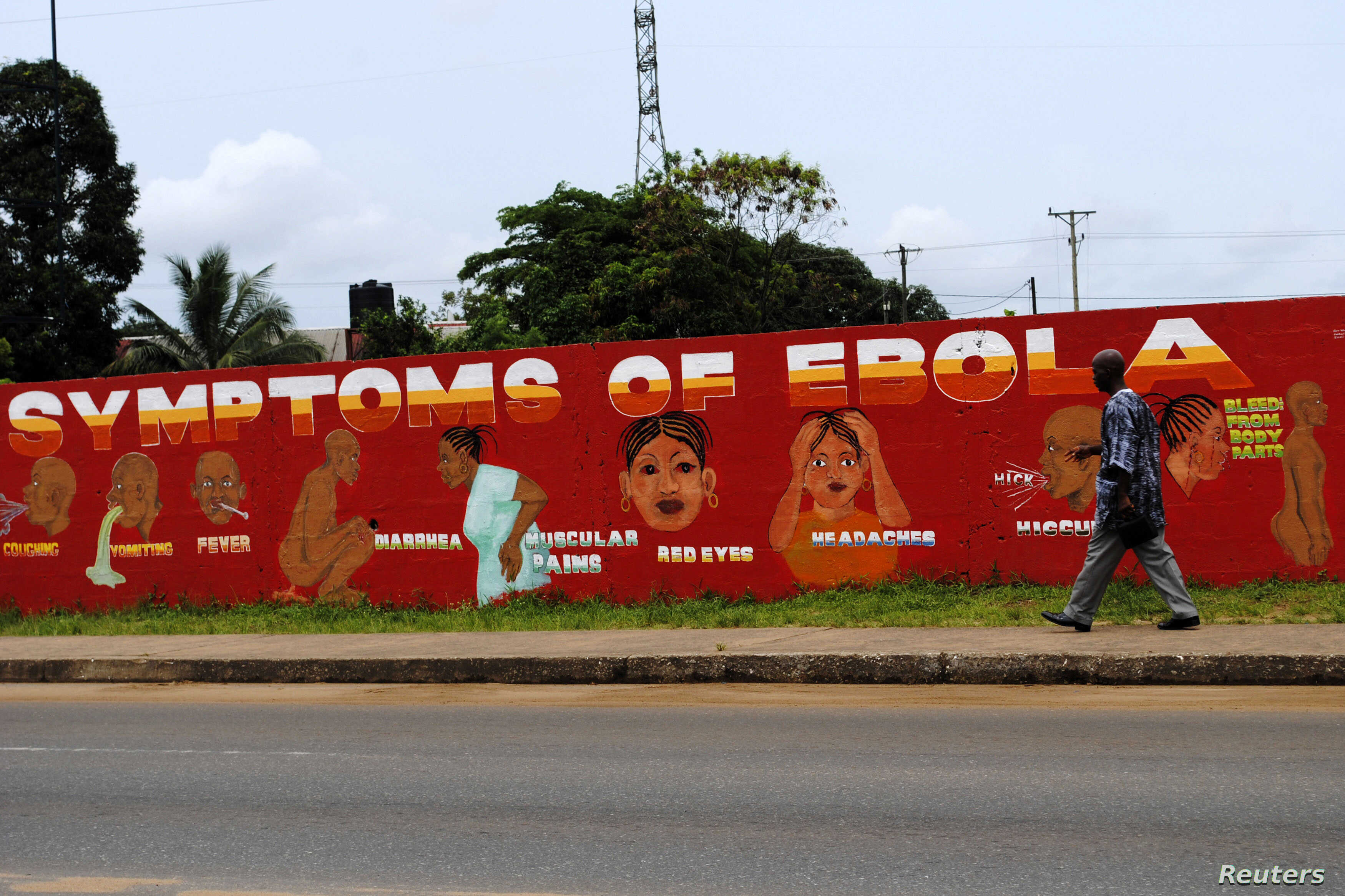 """A man walks by a mural that reads """"Symptoms of Ebola"""" in Monrovia, Liberia, Oct. 12, 2014."""