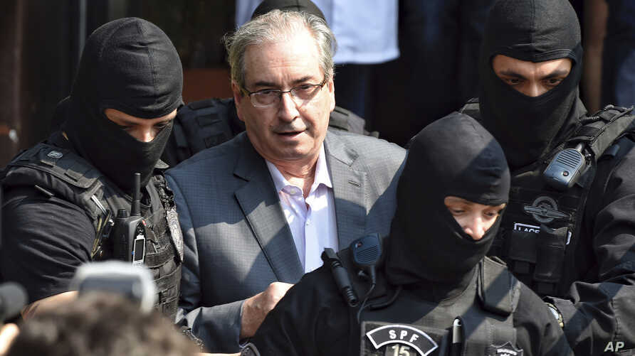 Eduardo Cunha, former speaker of Brazil's lower house, is escorted by federal police officers as he arrives to the Legal Medical Institute, in Curitiba, Brazil, Oct. 20, 2016.