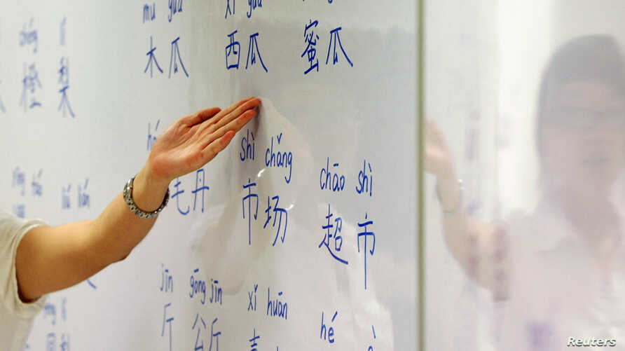 An instructor points out mandarin characters on a whiteboard at a night class for people learning mandarin as a second language in Singapore Sept. 1, 2009.