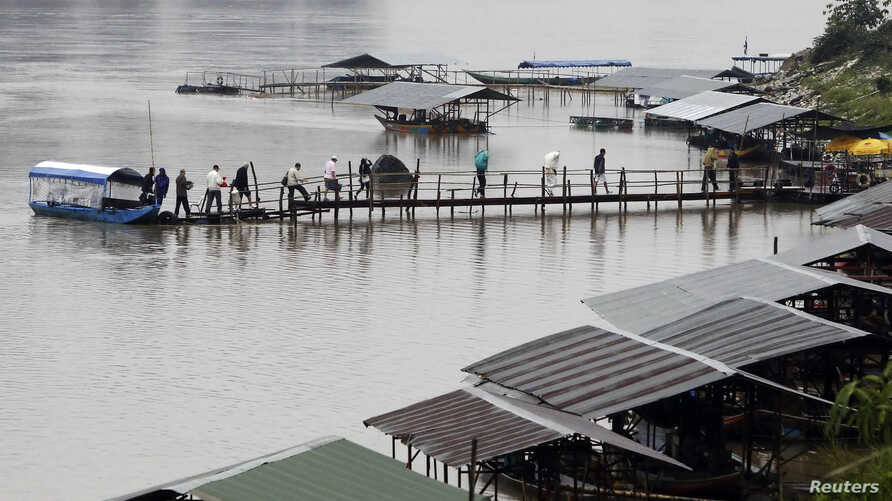 Tourists and gamblers disembark a boat on the Mekong River near the Thai port of Chiang Saen in the Golden Triangle region where the borders of Thailand, Laos, and Burma meet January 14, 2012.