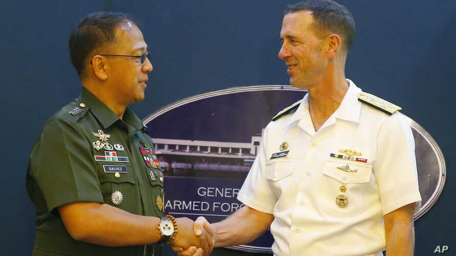 Philippine Armed Forces Chief Gen. Carlito Galvez Jr., left, and Adm. John Richardson, chief of Naval Operations of the U.S. Navy, shake hands prior to a news conference following their meeting at Camp Aguinaldo in suburban Quezon city, northeast of