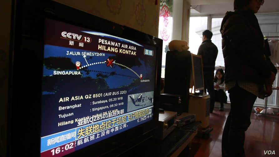 Relatives of the passengers on board the Malaysia Airlines Flight 370 that went missing on March 8, 2014 stand near a TV showing a live broadcast of the missing AirAsia Flight 8501 from Surabaya to Singapore, during their year-end gathering at a hous