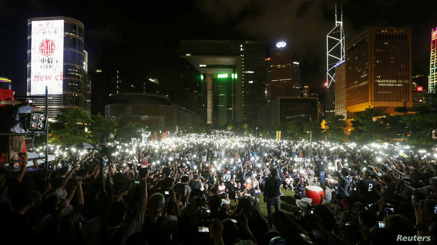 Pro-democracy protesters switch on their mobile phones during a campaign to kick off the Occupy Central civil disobedience event in front of the financial Central district in Hong Kong, Aug. 31, 2014.