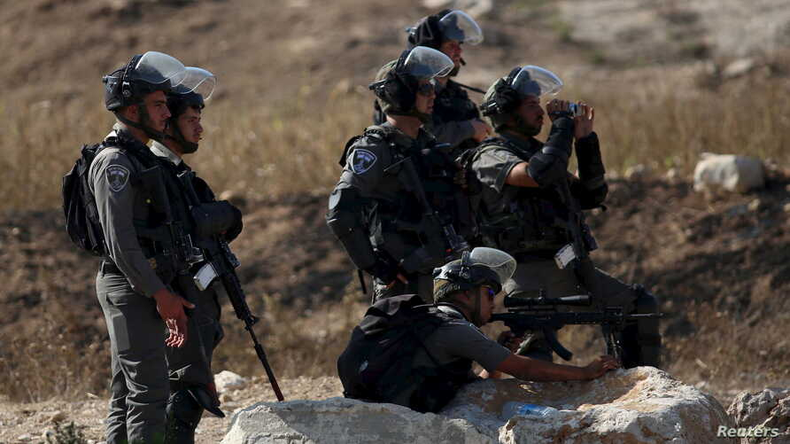 An Israeli border policeman aims his weapon at Palestinians during clashes at the Israeli Hawara checkpoint near the West Bank city of Nablus October 16, 2015. The unrest that has engulfed Jerusalem and the occupied West Bank, the most serious in yea