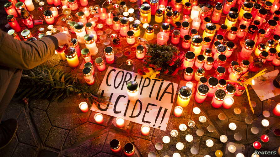 """FILE - A banner reading """"Corruption kills"""" is seen among candles, lit in memory of dozens of people killed in a night club fire in Bucharest, at a memorial in Timisoara, Romania, Nov. 1, 2015. Officials who secured an operating license for the club,"""