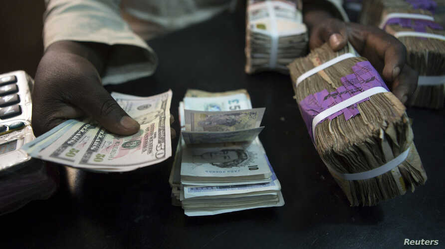 FILE - A trader changes dollars with naira at a currency exchange store in Lagos, Feb. 12, 2015.