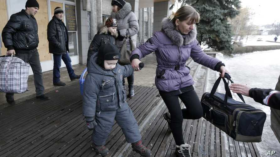 People carry their belongings as they walk to a bus to leave the town of Debaltseve, Ukraine, Saturday, Jan. 31, 2015.