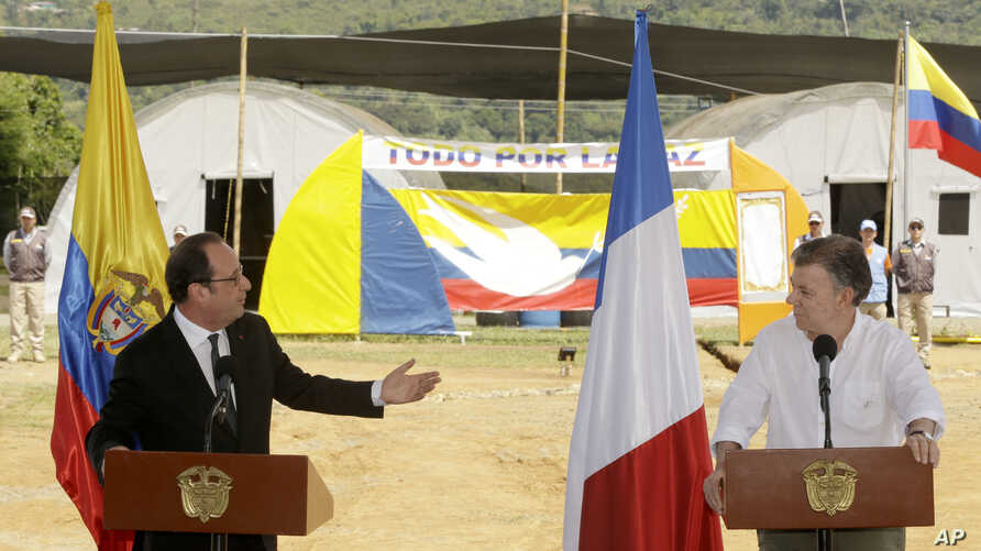 France's President Francois Hollande, left, speaks during a joint statement with Colombia's President Juan Manuel Santos, right, during a visit to a United Nations camp near an area where members of FARC, will turn over weapons to U.N. observers in L